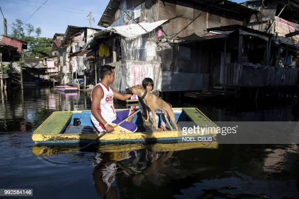 Residents ride on a makeshift boat to cross stagnant floodwaters in the Artex Compound in Manila on July 6, 2018. - Health officials have said that...