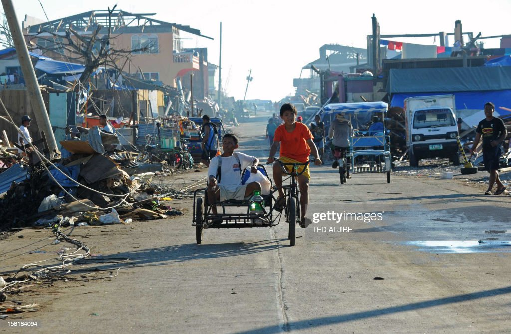 Residents ride on a tricycle past debris littered along a street in Cateel town, Davao Oriental province on December 11, 2012, in the aftermath of Typhoon Bopha. The United Nations launched a 65 million USD global appeal on December 10 to help desperate survivors of a typhoon that killed more than 600 people and affected millions in the southern Philippines.