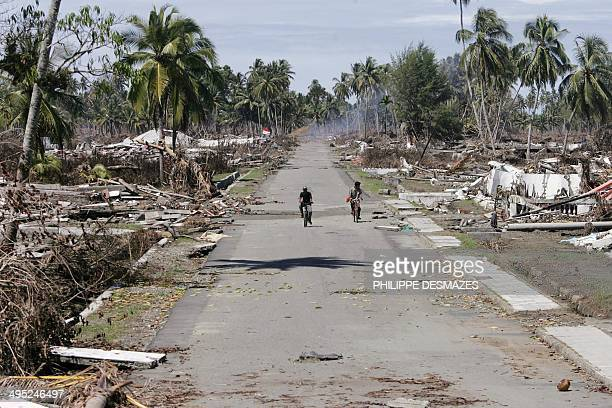 Residents riding on a bicycle survey destroyed house in Meulaboh 12 January 2005 Indonesia on Wednesday stood firm on tough restrictions for foreign...