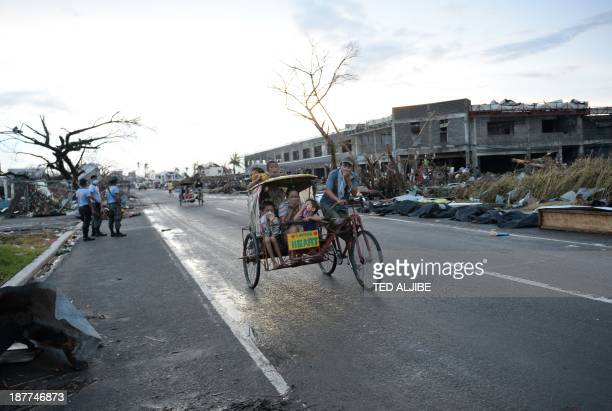 Residents riding on a tricycle cover their faces from the smell of cadavers along a road in Tacloban city, Leyte province central Philippines on...