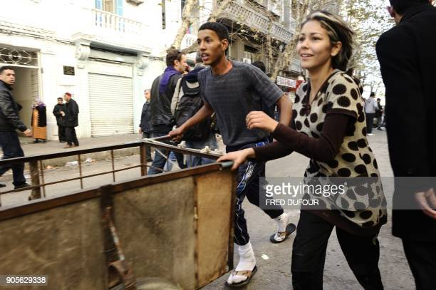 Residents run to take goods from a destroyed store in Tunis on January 15 2011 There were scenes of looting overnight in the suburbs of Tunis...