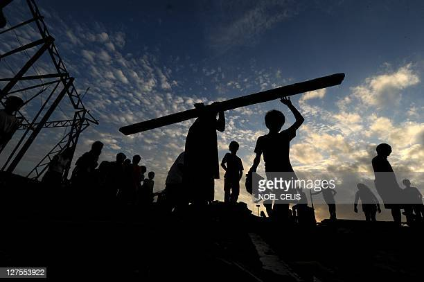 Residents salvage housing materials from a community on Manila Bay in Navotas, part of Metro Manila, on September 29, 2011 in an area that was...