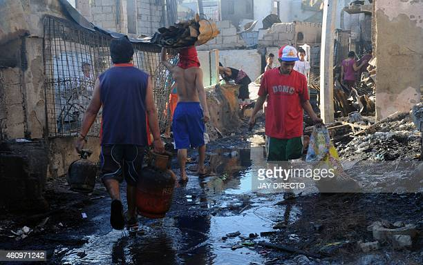 Residents salvage usable material at the site of a fire in a shanty town in Manila on January 2 2015 A fire raced through a crowded slum in the...