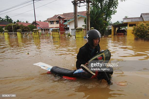 Residents save themselves from floods at Pangkalan village on February 08 2016 in Lima Puluh Koto regency West Sumatra Province Indonesia More 1000...