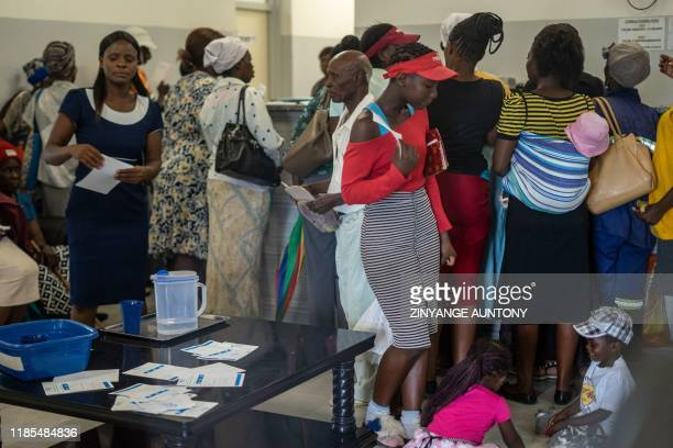 Residents scramble for service at the West Memorial Clinic in the Cowdray Park township, Bulawayo, in Zimbabwe on November 22, 2019. -...