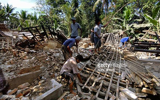 Residents search the wreckages of a house after a powerful eathquake in Bantulm, 27 May 2006. At least 1,971 people were killed and thousands injured...
