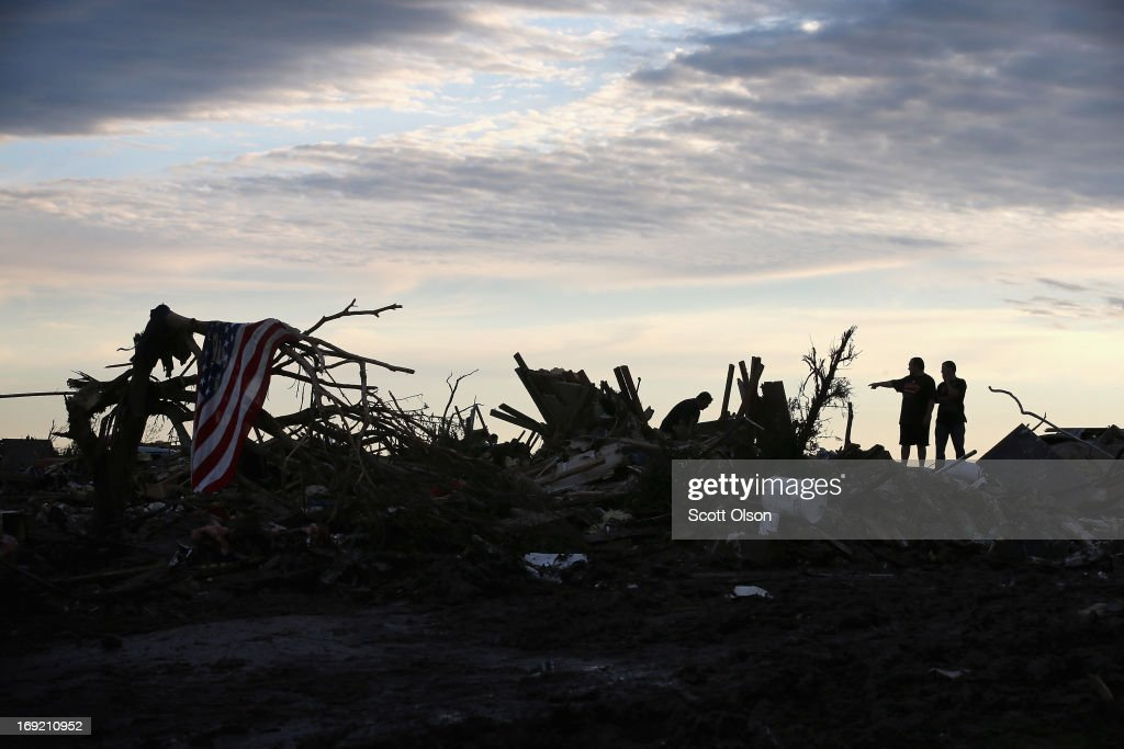 Residents search through rubble after a powerful tornado ripped through the area on May 21, 2013 in Moore, Oklahoma. The town reported a tornado of at least EF4 strength and two miles wide that touched down yesterday killing at least 24 people and leveling everything in its path. U.S. President Barack Obama promised federal aid to supplement state and local recovery efforts.