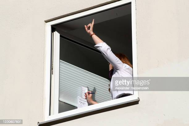 Residents seen as performing artist Max Auerbach announces bingo numbers to participants playing from their balconies during the novel coronavirus...