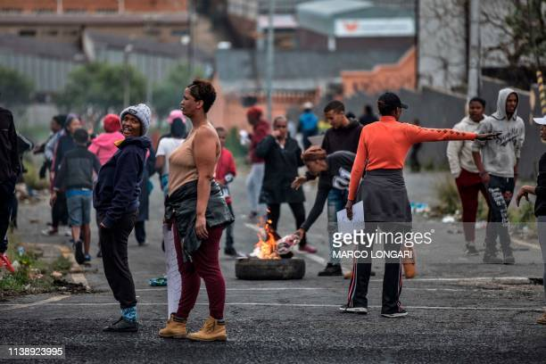Residents set a tyre on fire in the street of Johannesburg on April 23 2019 during a protest against the lack of service delivery or basic...