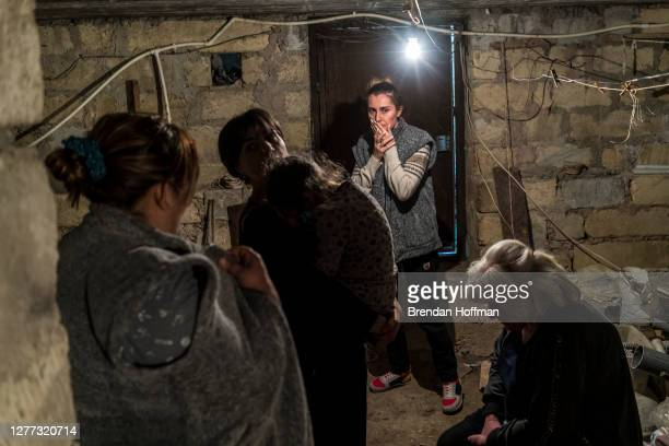 Residents shelter in a basement as air raid sirens sound on September 29, 2020 in Stepanakert, Nagorno-Karabakh. A decades-old conflict between...