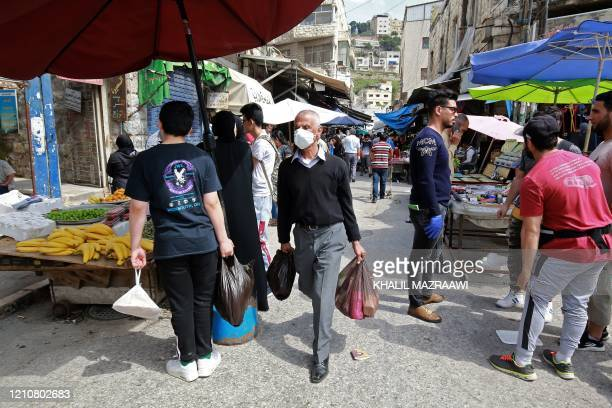 Residents shop at a market ahead of the Muslim holy month of Ramadan during the novel coronavirus pandemic crisis in the Jordanian capital Amman on...