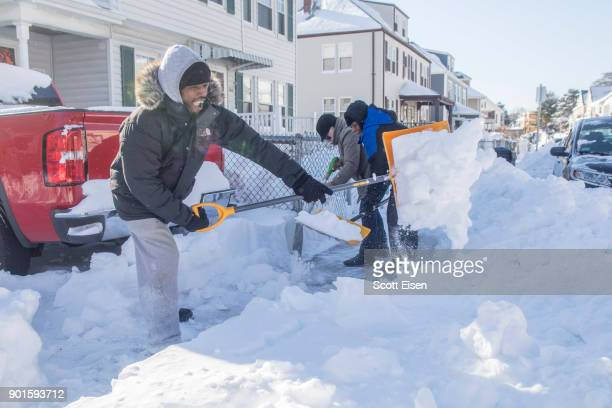 Residents shovel out their vehicle and sidewalk the day after the region was hit with a 'bomb cyclone' on January 5 2018 in the Dorchester...