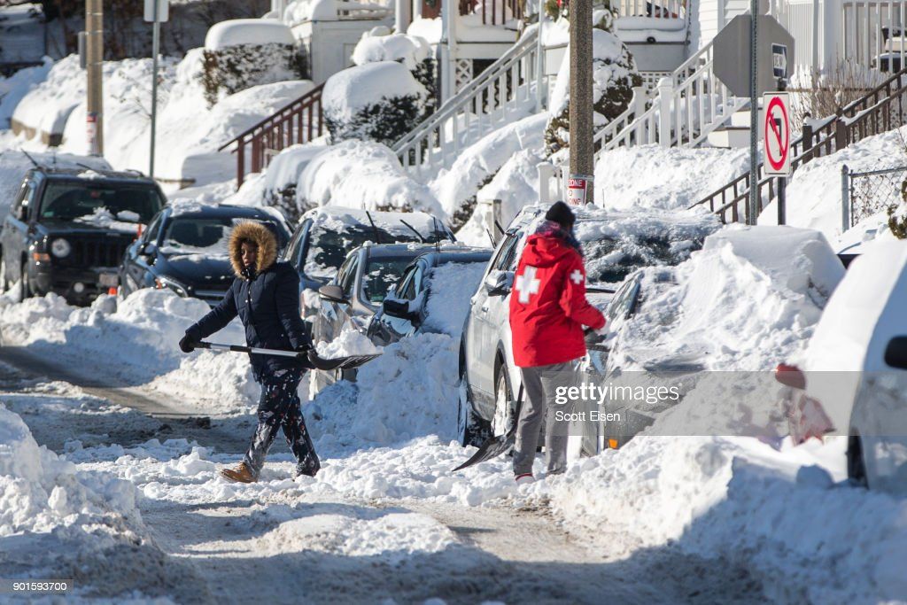 Residents shovel out their vehicle the day after the region was hit with a 'bomb cyclone' on January 5, 2018 in the Dorchester neighborhood of Boston, Massachusetts. Schools and businesses throughout the Boston area get back to work today after the city received over a foot of snow during the fast moving storm yesterday.