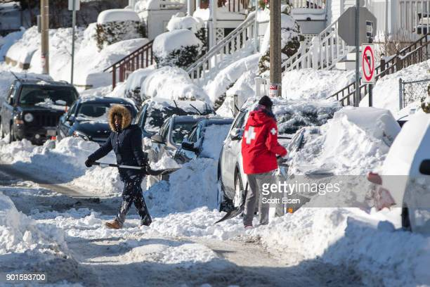 Residents shovel out their vehicle the day after the region was hit with a bomb cyclone on January 5 2018 in the Dorchester neighborhood of Boston...