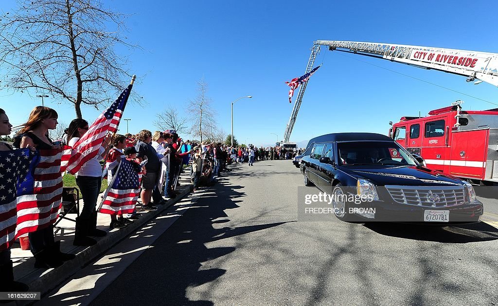 Residents show their support as watch the departure of the hearse carrying the body of slain Riverside police officer Michael Crain in a convoy following a memorial service at the Grove Community Church in Riverside, California, on February 13, 2013. Law enforcement personnel from across the state, including local dignitaries, military veterans, colleagues, friends and loved ones of Crain gathered to pay their final respects to the policeman killed last week in what the city's police chief described as a 'cowardly ambush.'' Crain was fatally shot February 7 when he and his partner ran afoul of fugitive Christopher Jordan Dorner. AFP PHOTO / Frederic J. BROWN