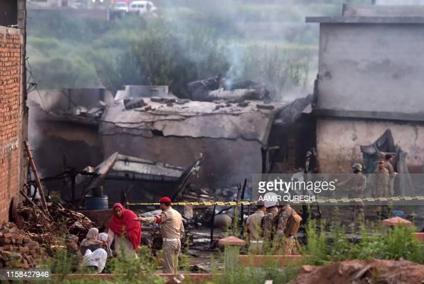 TOPSHOT Residents sit among the rubble of their destroyed house as soldiers cordon off the site where a Pakistani Army Aviation Corps aircraft...