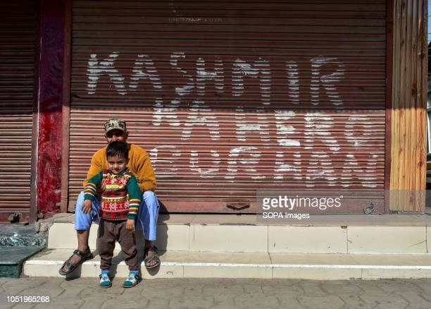 Residents sit in front of a closed shop painted with a graffiti during restrictions in Srinagar Indian administered Kashmir Authorities impose...