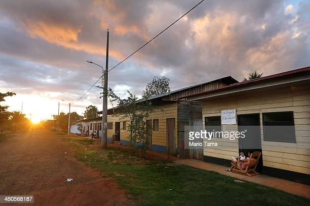 Residents sit in front of their home at sunset in a deforested section along the Interoceanic Highway in the Amazon lowlands on November 18 2013 in...