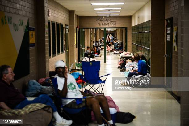 Residents sit in the hallway of a temporary Red Cross shelter at Conway High School ahead of Hurricane Florence in Conway South Carolina US on...
