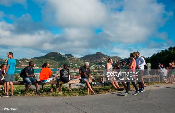 Residents sit on a road barrier overlooking the SaintJeanGustave III airport on the French Caribbean island of SaintBarthelemy on December 10 prior...