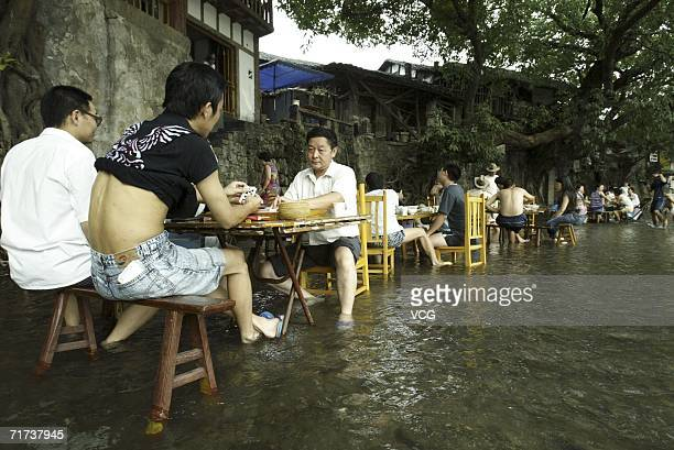 Residents sit on chairs in a river playing Mahjong to keep cool on August 29 2006 in Chongqing China Continued hot weather in southern China is...