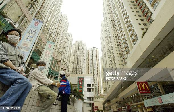 Residents sit ouside the Amoy Gardens housing estate in Kowloon bay, Hong Kong where a block has been quarantined to protect against a deadly...