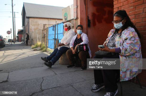 Residents sit outdoors on the sidewalk amid a surge of coronavirus cases in the city on November 18, 2020 in El Paso, Texas. Texas surpassed 20,000...