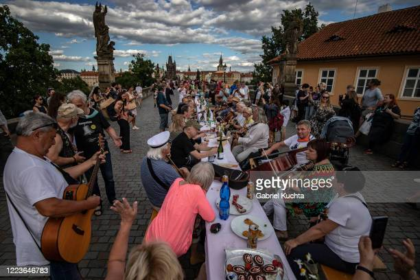 Residents sit to dine on a 500 meter long table set on the Charles Bridge after restrictions were eased following the coronavirus pandemic on June 30...
