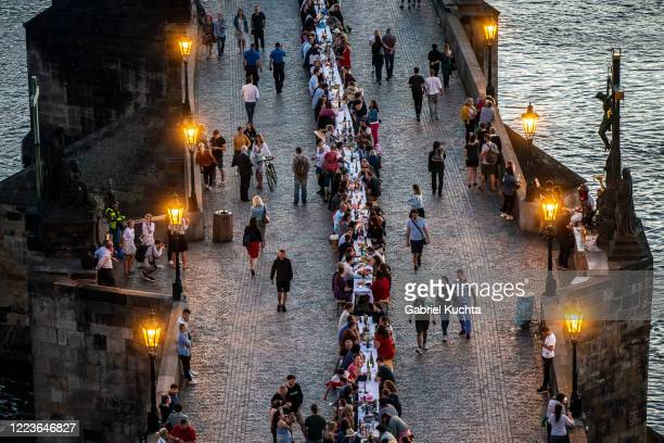 Residents sit to dine on a 500 meter long table set on the Charles Bridge, after restrictions were eased following the coronavirus pandemic on June...