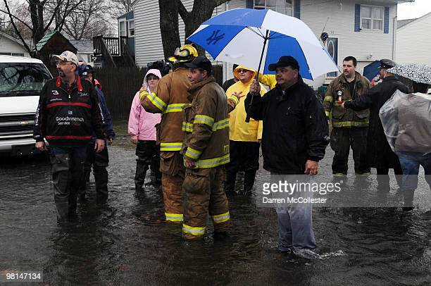 Residents speak with firefighters as they deal with flooding issues on Moore and Perkins Street deal March 30 2010 in Cranston Rhode Island The...