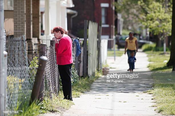 Residents stand along Seymour Avenue across the street from the house where three women who disappeared as teens about a decade ago were found alive...