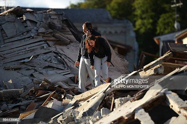 TOPSHOT Residents stand among damaged buildings after a strong earthquake hit Amatrice on August 24 2016 Central Italy was struck by a powerful...