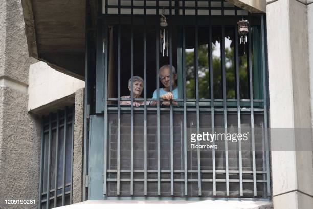 Residents stand at a window while listening as a priest delivers blessings from a vehicle during Palm Sunday in Caracas Venezuela on Sunday April 5...