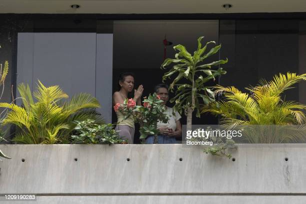 Residents stand at a window while praying as a priest delivers blessings from a vehicle during Palm Sunday in Caracas Venezuela on Sunday April 5...