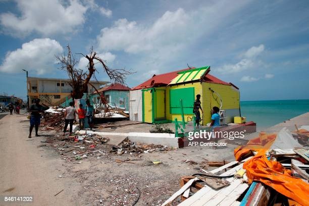 TOPSHOT Residents stand beside the wreckage of their destroyed homes on the French Caribbean island of Saint Martin during the visit of French...