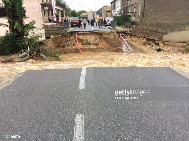 TOPSHOT Residents stand by a broken bridge on the river Trapel following floods on October 15 2018 in Villegailhenc near Carcassone southern France...