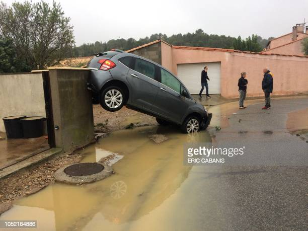 TOPSHOT Residents stand by a car swept away by floods on October 15 2018 in Villegailhenc near Carcassone southern France Six people died following...