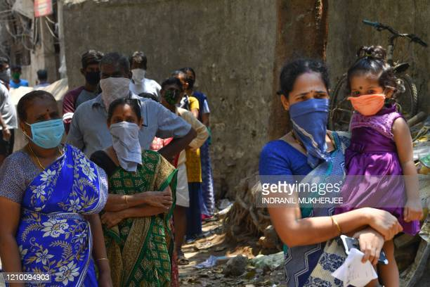 Residents stand in a queue to get tested for the the COVID19 coronavirus inside Dharavi slums during a governmentimposed nationwide lockdown as a...