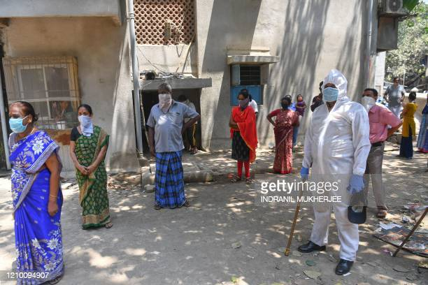 Residents stand in a queue to get tested for the the COVID-19 coronavirus inside Dharavi slums during a government-imposed nationwide lockdown as a...