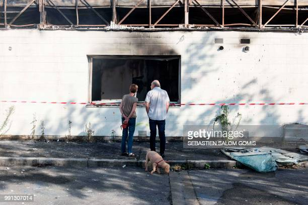Residents stand in front of a burned medical center on July 4 2018 in the Breil neighborhood of Nantes following clashes between groups of young...