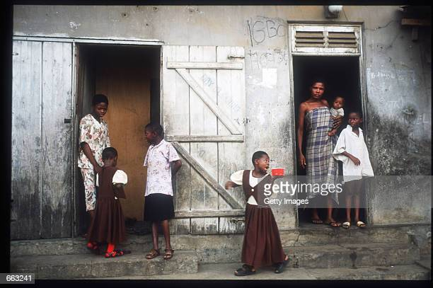 Residents stand in front of homes December 15 1999 in the Ajegunle area of Lagos Nigeria Signs painted on the fronts of the houses indicate that the...