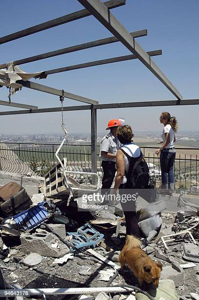 Residents stand in the rubble of a home after it was hit by a Hezbollah rocket in the northern town of Haifa Israel on Sunday July 23 2006 Six...