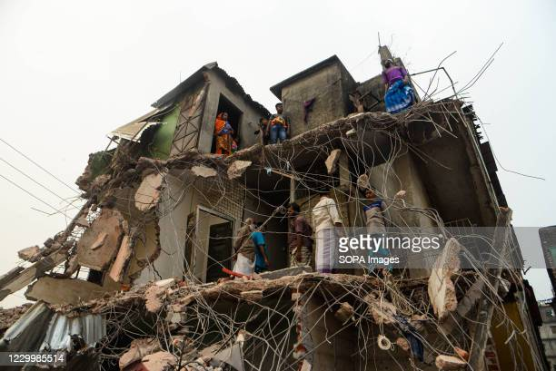 Residents stand in their demolished house. Bangladesh Inland Water Transport Authority conducts a drive to evict illegal structures from the bank of...