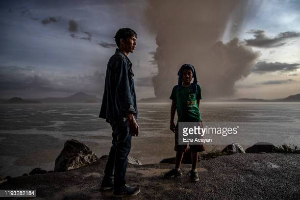 Residents stand near a lakeside as Taal Volcano erupts on January 12 2020 in Talisay Batangas province Philippines Local authorities have begun...