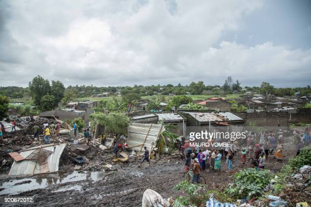Residents stand near the site of a dump collapse in a poor district of Maputo on February 19 2018 At least 17 people were killed when a rubbish mound...