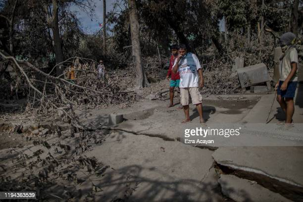 Residents stand next to a fissure on the ground caused by Taal Volcano's eruption on January 18 2020 in Talisay Batangas province Philippines The...
