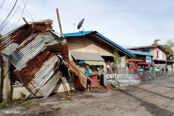 TOPSHOT Residents stand next to a house damaged by typhoon Phanfone in Ormoc City Leyte province in central Philippines on December 25 2019 Typhoon...