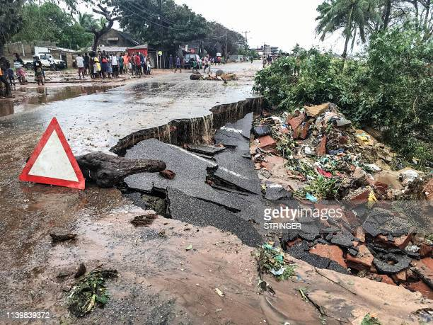 Residents stand next to a road partially destroyed by floods after heavy downpours in Pemba, on April 28 after the destruction caused by Cyclone...