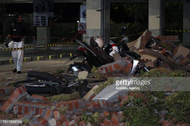 Residents stand next to bikes and debris at a mall after a magnitude 70 earthquake rocked neighbouring Lombok island in Bali's capital Denpasar...