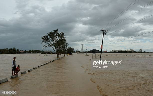 Residents stand on a flooded highway in Santa Rosa town Nueva Ecija province north of Manila on October 19 a day after typhoon Koppu hit Aurora...